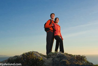 An Hispanic couple is hugging on a mountain top near Buenos Aires. The young romantic couple is backed by a clear deep blue sky. They are wearing bright orange clothing and backpacks. The couple has stopped to watch the sunset.